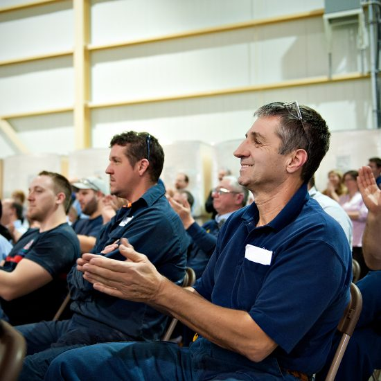 Employees applauding at company meeting